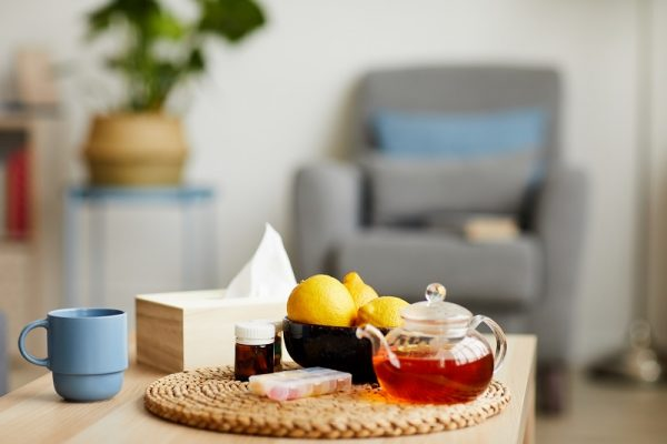 Image of hot tea with lemons and pills on the table preparing to treat colds at home